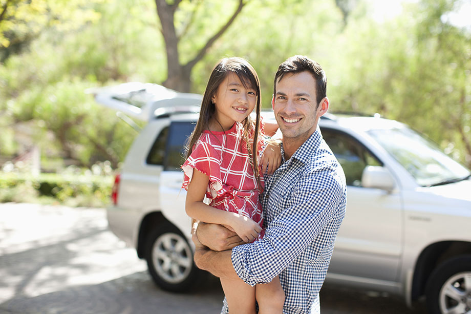 father and daughter standing in front of car